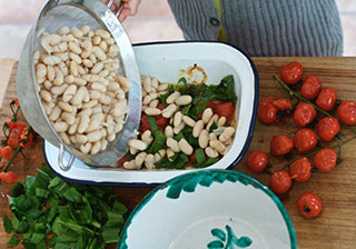 Pouring beans into a container of Bean Salad, tomatoes and herbs on the table beside it