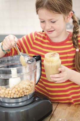 A young girl spooning ingredients into a food processor