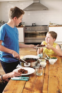 Children sitting around a table, one child spooning out a meal onto a dish and handing it to a younger child