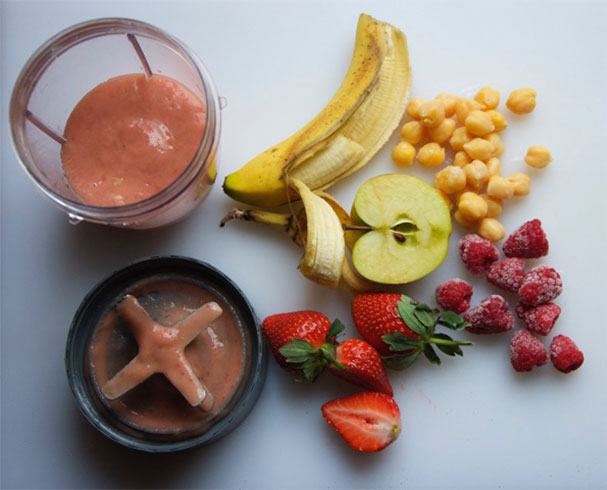 Smoothie ingredients, including chickpeas, on a table with a blender