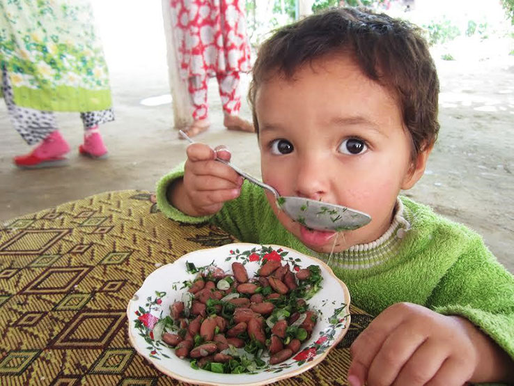 Child in Tajikistan eating a bowl of beans