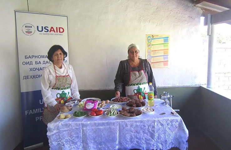 Two ladies standing behind a table of food and a US AID poster for a recipe book they helped develop