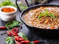 Thumbnail of a decorated bowl of lentils and red chili peppers on a table