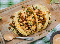 5 healthy lentil tacos fanned out on a wood board, with a spoon of sauce placed beside them