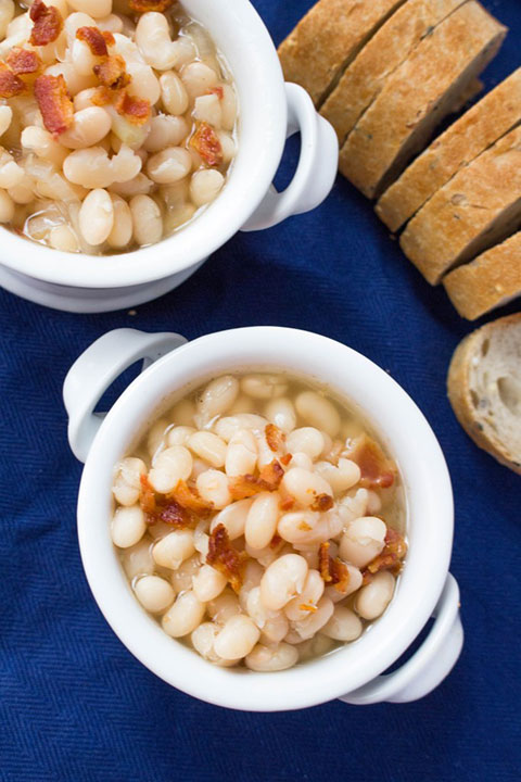 Carmy's Tuscan Bean Soup with bacon crumbled on top and a loaf of bread in the background