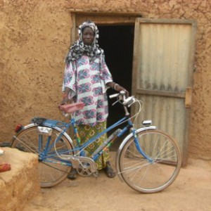 Azeta poses with the bike she was able to purchase thanks to her niébé sales. Copyright: WFP
